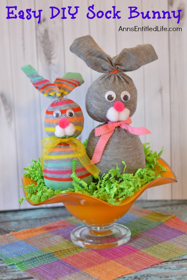 two sock bunnies in an orange bowl on top of green Easter grass