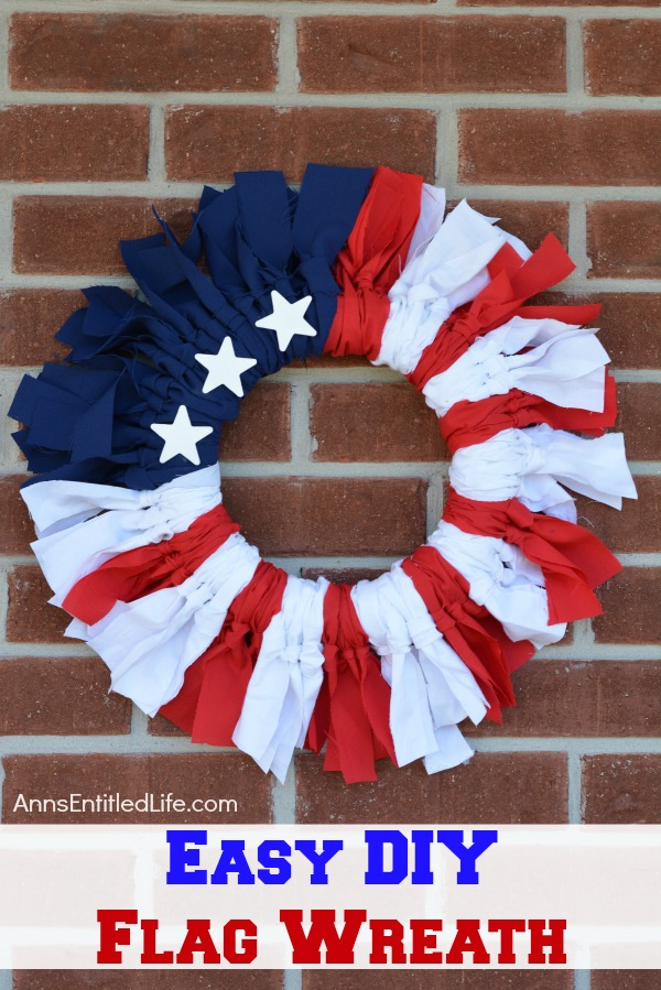 A red, white, and blue wreath with several stars hanging on a brick wall