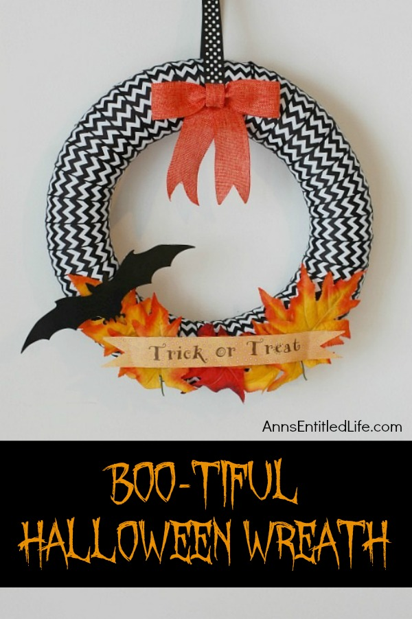 A Halloween wreath done in black and white ribbon, with a bat, bow, and leaves accent, hanging on a white wall.