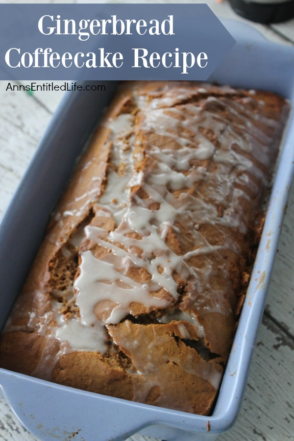A loaf of iced gingerbread coffee cake in a blue loaf pan on a battered blue countertop.