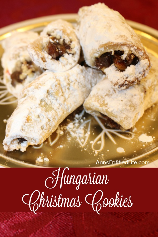A cgold plate filled with Hungarian Christmas cookies covered in powdered sugar