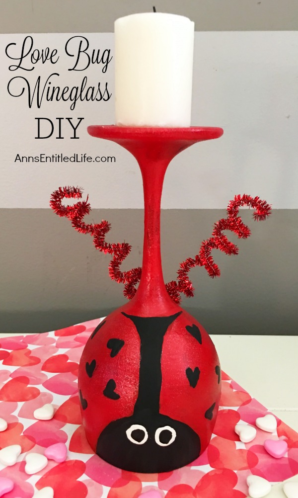 upside down wineglass painted like a love bug with antena and a candle, on top of a heart paper