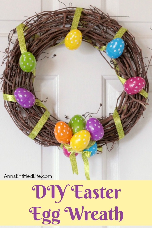 a grapevine Easter wreath decorated with eggs and ribbon hanging against a white door