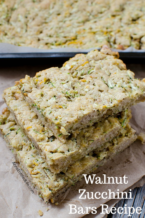 a stack of walnut zucchini bar squares on a napkin, the rest of the pan is in the background