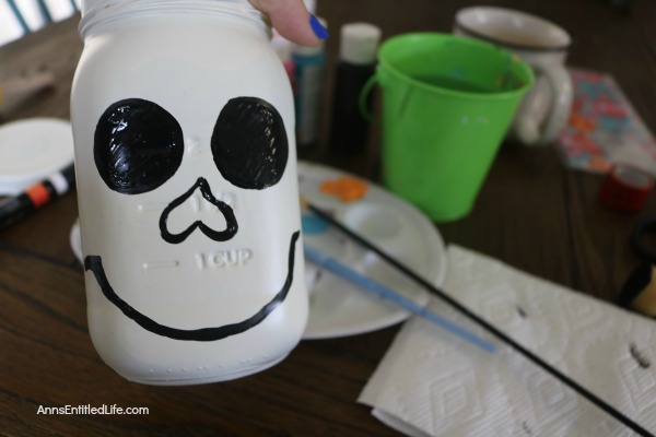 Sugar Skull Mason Jar Craft. This easy to make sugar skull is fashioned from an old Mason jar.  You can store kitchen utensils, candy (keep the lid!), etc in these jar for Halloween or to celebrate the Day of the Dead. Using old glass jars is a great way to get crafty at home and make your own cute décor at the same time.