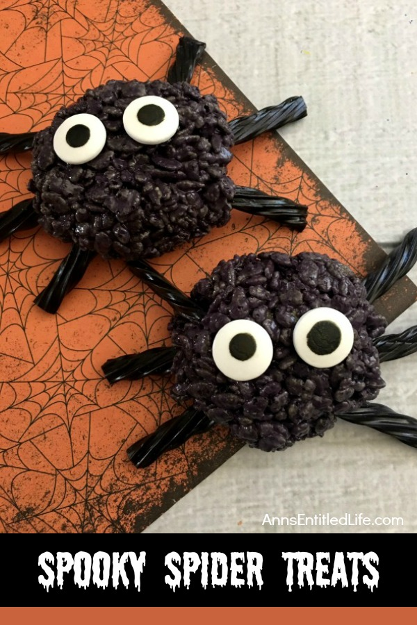 Two black crispy rice spiders set on an orange and black Halloween mat.