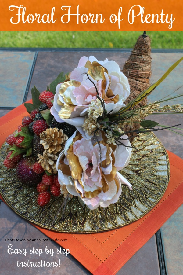 a twine horn of plenty stuffed with floral and beaded grapes sitting on a gold placemat which is sitting on an orange placemat