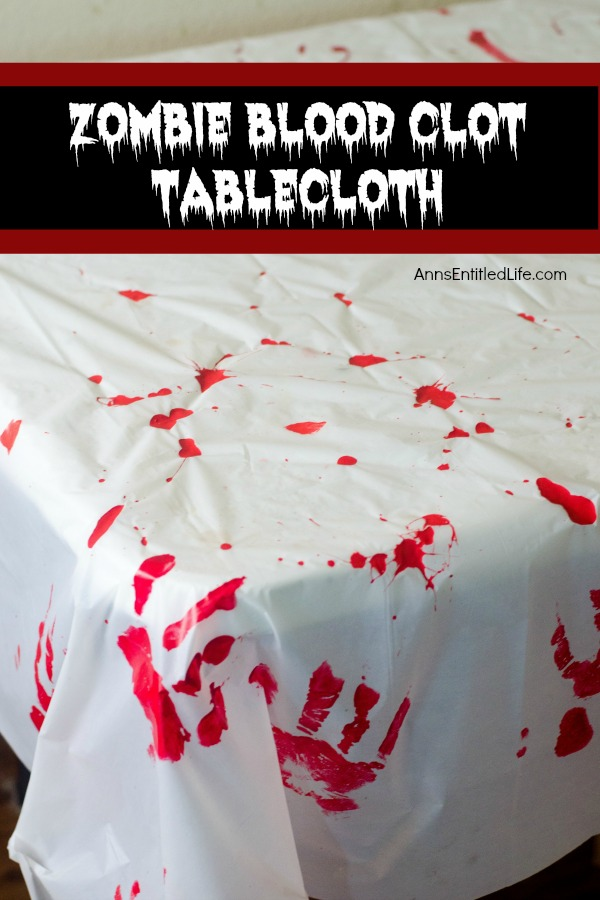 A white tablecloth with red handprints and