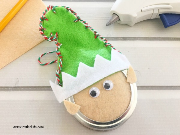 Elf Mason Jar Lid Ornament DIY. This easy to make Elf Mason jar lid ornament is simply adorable. This step by step tutorial has easy to follow directions so you can make one for your tree, to give as a gift, or to place on top of a present as a little something extra.