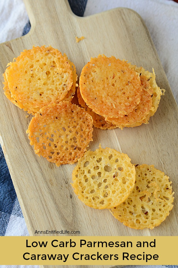 cheese cracker chips on a wooden cutting board over a blue kitchen towel