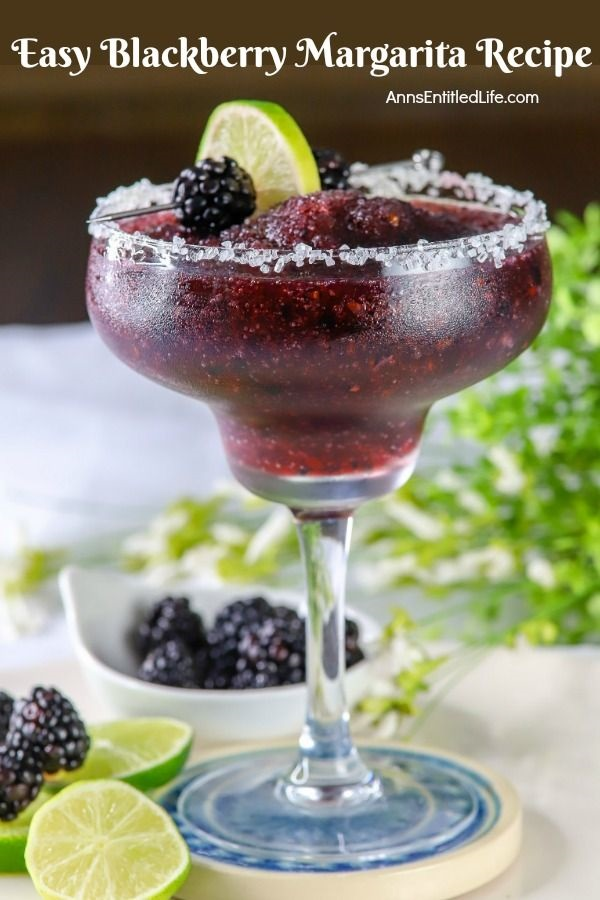 Side view of a blackberry margarita in a glass, a lime and fresh blackberry garnish on a skewer lays across the back. Below is a bowl of fresh blackberries, and more sliced limes
