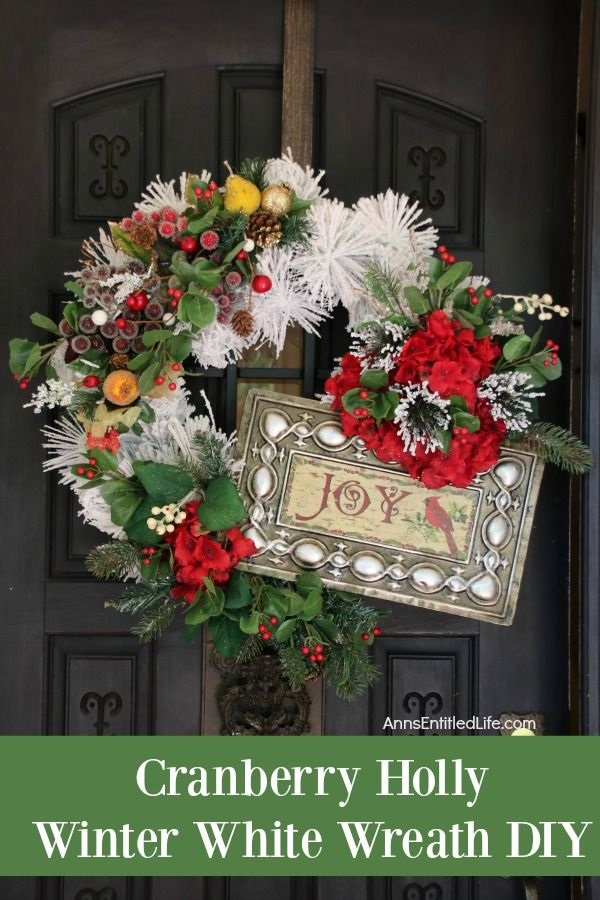 A large white wreath decorated with a sign, holly berries, and faux greenery handing on a bronze wreath hanger against a dark door.