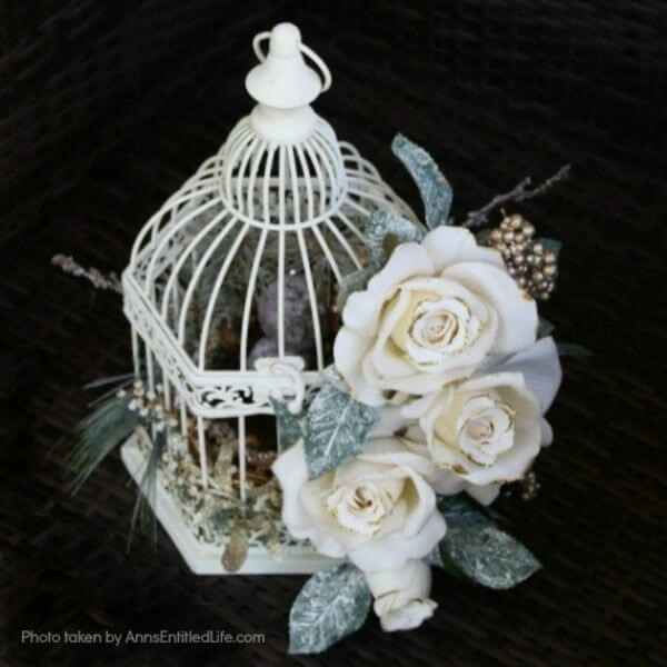 Have an old birdcage lying about that you would like to repurpose into a beautiful decor piece? This wonderful winter white birdcage decorating idea is a lovely DIY decorating piece for the holidays and beyond. This tells the story of a bird that has left the cage to fly south for the winter. His (or her) nest is empty, and he (or she) is off to parts unknown. This is not only a lovely winter piece, it could be used for wedding decor, a centerpiece, a front foyer piece (I always decorate my foyer!) or you could hang it as an empty birdcage in a Florida room or family room.