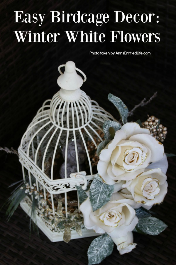 A white bird cage decorated with faux white flowers and greenery against a black background