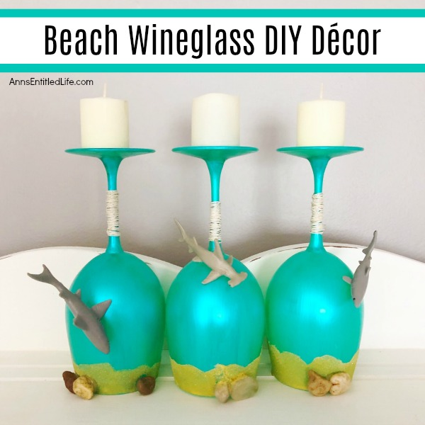 Beach Wineglass DIY Décor. Make your own beach themed wineglasses with these easy step-by-step tutorial instructions. This is a great summertime craft, makes a fabulous shark week decoration, or if you have beach themed décor in your home or on your lanai, patio or in your three-season room, this is a fun and funky craft project to add to it. These highly customizable beach wineglasses are simple to make and will look great on your mantel, side table or as part of a larger décor theme.