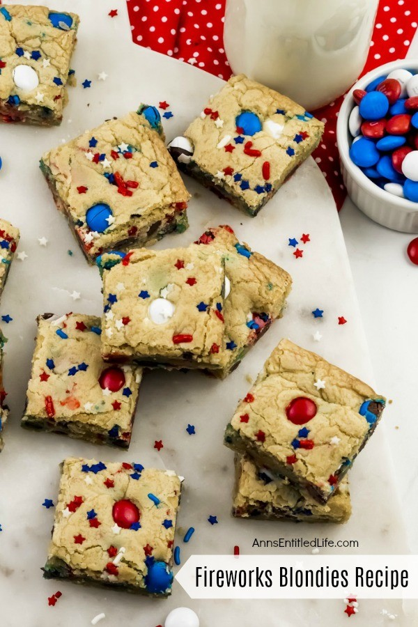 festive red, white, and blue blondies bars on a white plate, M&Ms upper right, milk glass on red polka dot napkin also in the upper right