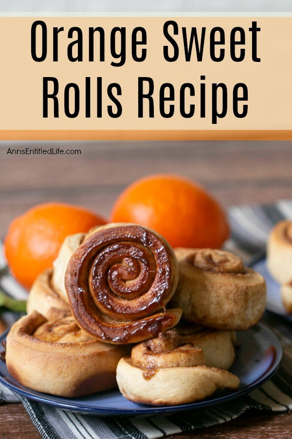 six orange sweet rolls on a blue plate, two fresh oranges in the background