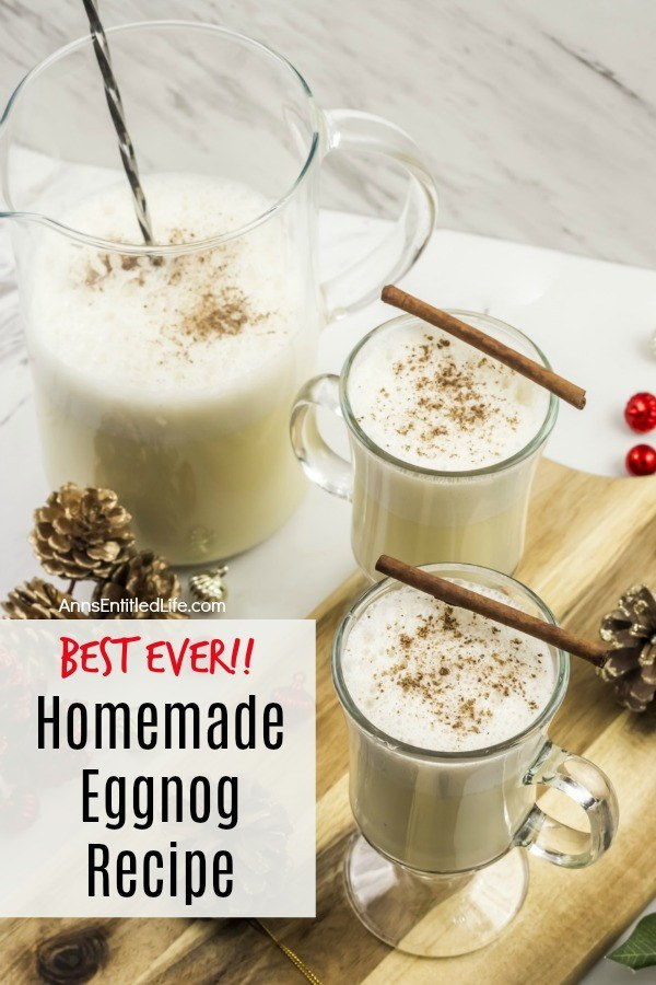 pitcher of homemade eggnog and two poured glasses on a butcher block, with pinecone and red bulbs scattered about