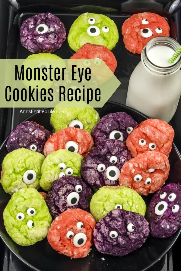multicolored cookies with candy eyeballs on a dark tray, a bottle of milk wth a straw is in the upper right