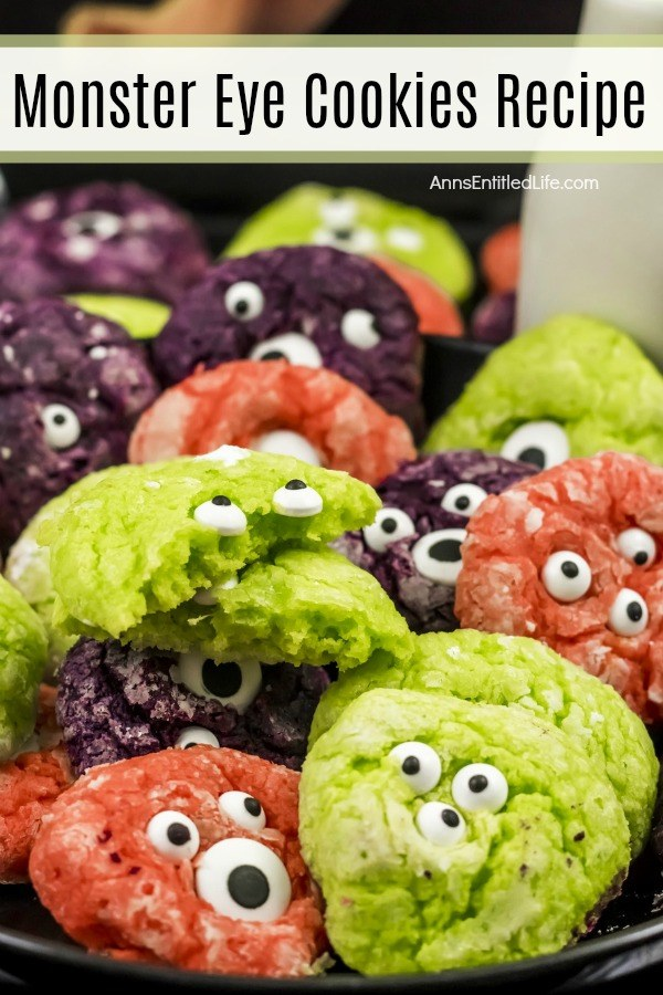 multicolored crinkle cookies with candy eyeballs in them on a dark tray