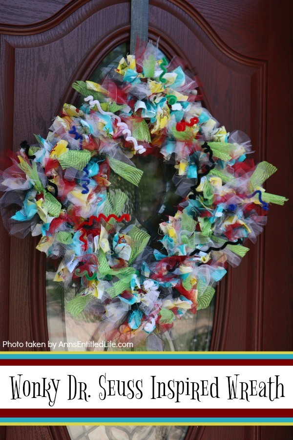 multicolored wreath with a Dr. Seuss theme hung diagonally on a brown front door with a window
