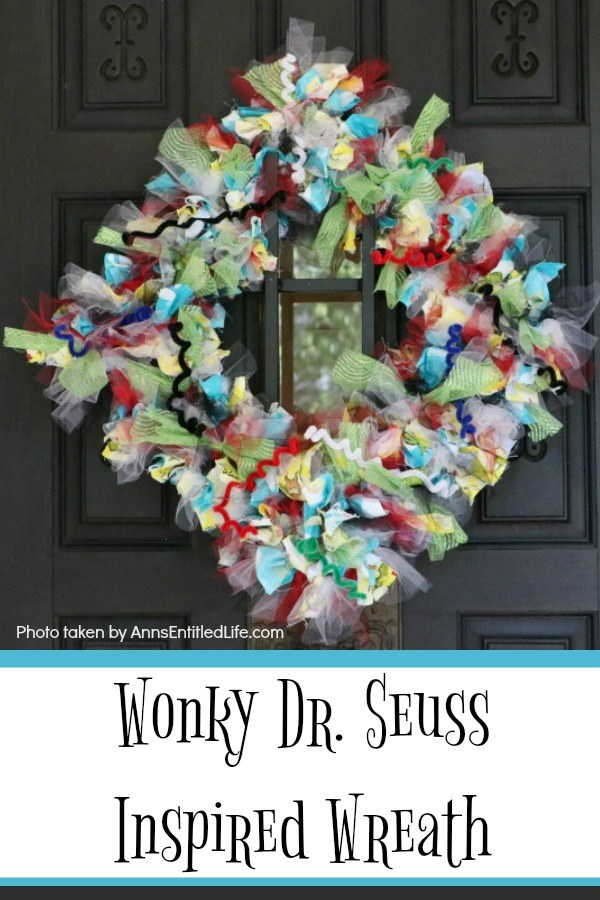 multicolored wreath with a Dr. Seuss theme hung diagonally on a dark-colored front door