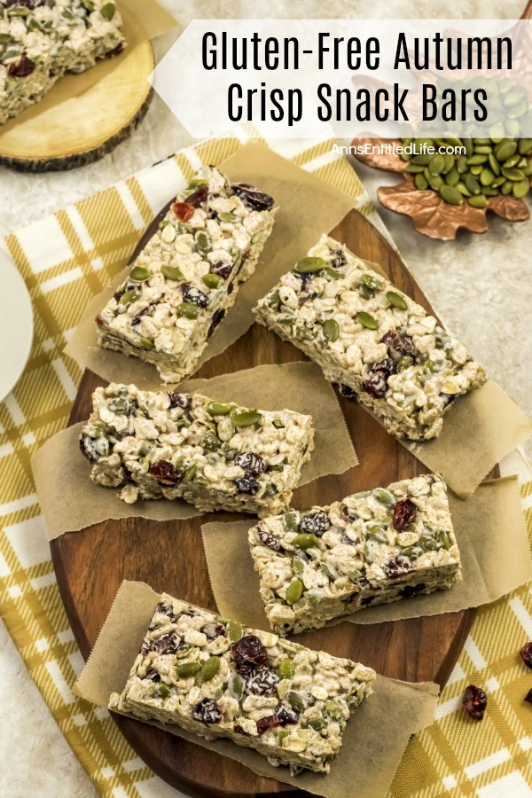 5 Gluten-Free Autumn Crisp Snack Bars served on small pieces of butcher paper, on a brown cutting board atop a yellow and white dish towel, a dish of pepitas is in the upper right, another snack bar sits on a wooden tray in the upper left