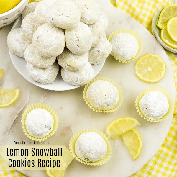 5 lempon snowball cookies in yellow cupcake holders, a white plate full of lemon snowball cookies in the upper left. Fresh lemons are displayed as garnish. All sits on a white board