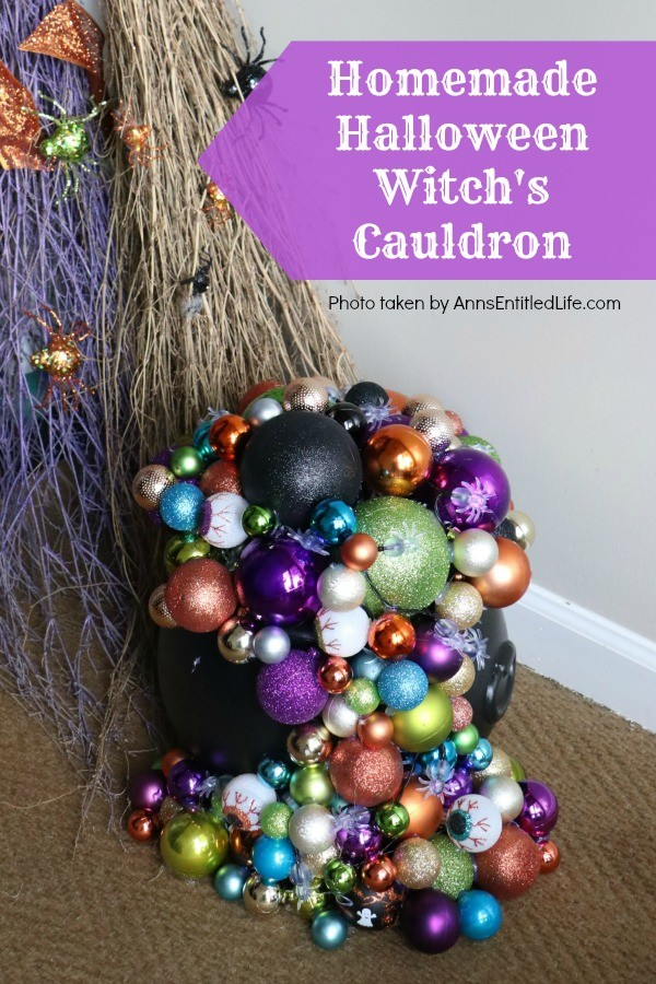 multicolored bulbs formed to imitate bubbles flowing from the cauldron base. There are two cauldrons, one large, one small. Two decorated broom are in the background, indoors on a tan rug