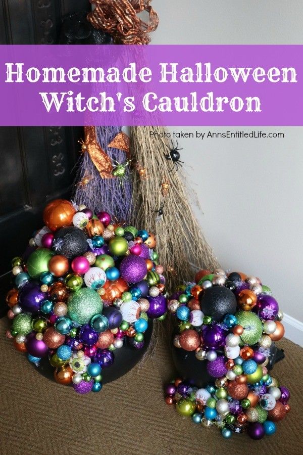 multicolored bulbs formed to imitate bubbles flowing from the cauldron base. There are two cauldrons, one large, one small. Two decorated brooms are in the background, outside on a porch