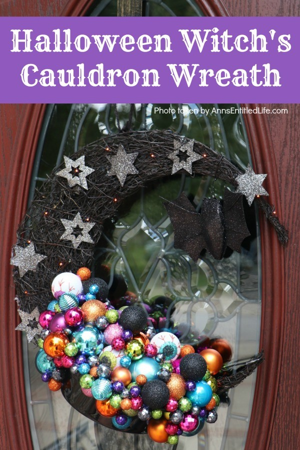 multicolored bulbs formed to imitate bubbles flowing from the cauldron attached to a half-moon black prelit wreath, hanging on a brown door with a glass insert