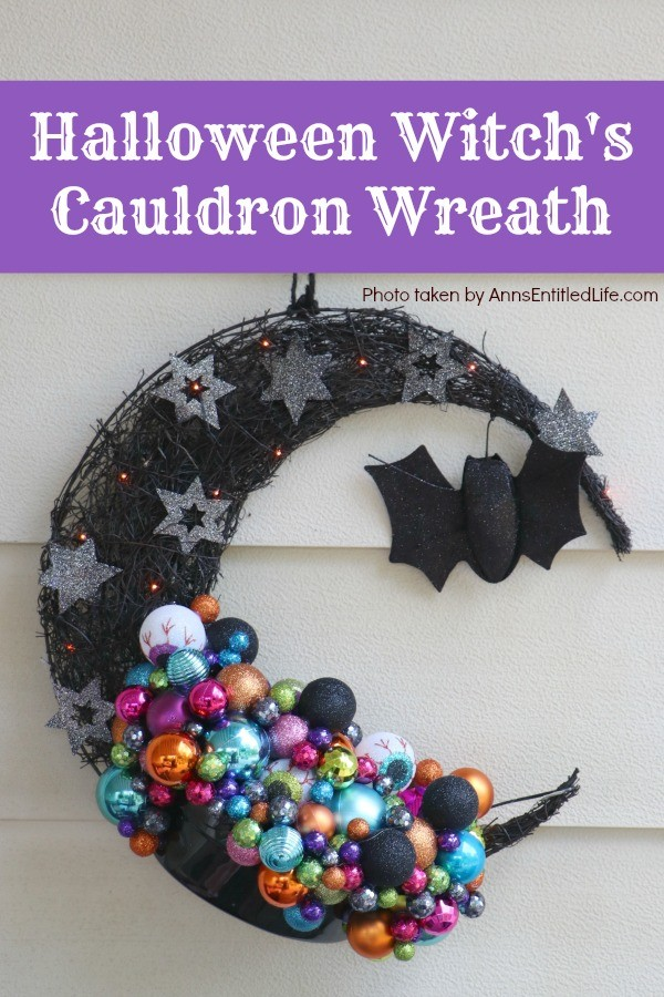 multicolored bulbs formed to imitate bubbles flowing from the cauldron attached to a half-moon black prelit wreath, hanging on a yellow