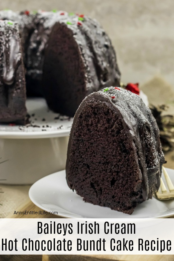 A slice of Baileys Irish Cream Hot Chocolate Bundt Cake sitting on a white plate. The remaining bundt cake is in the upper left. These are set upon a beige placemat.