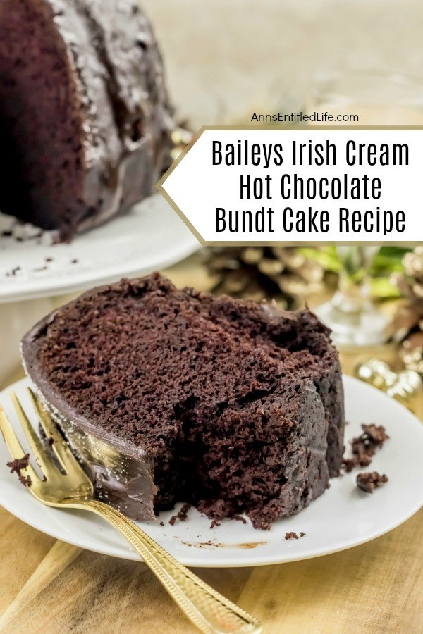 A slice of Baileys Irish Cream Hot Chocolate Bundt Cake laying on its side on a white plate, a bite is missing, There is a gold fork on the left side of the plate. The remaining bundt cake is in the upper left. These are set upon a beige placemat.