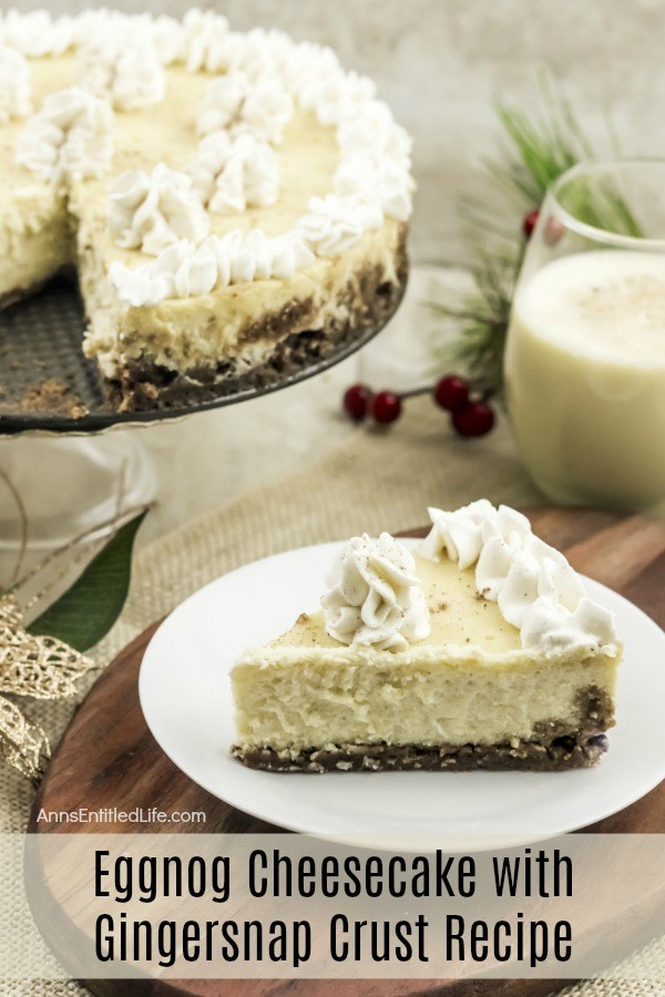A slice of eggnog cheesecake on a white plate is front and center, the remaining eggnog cheesecake sits in the upper left. There is a glass of eggnog in the upper right. Holiday decorations make the scene festive.