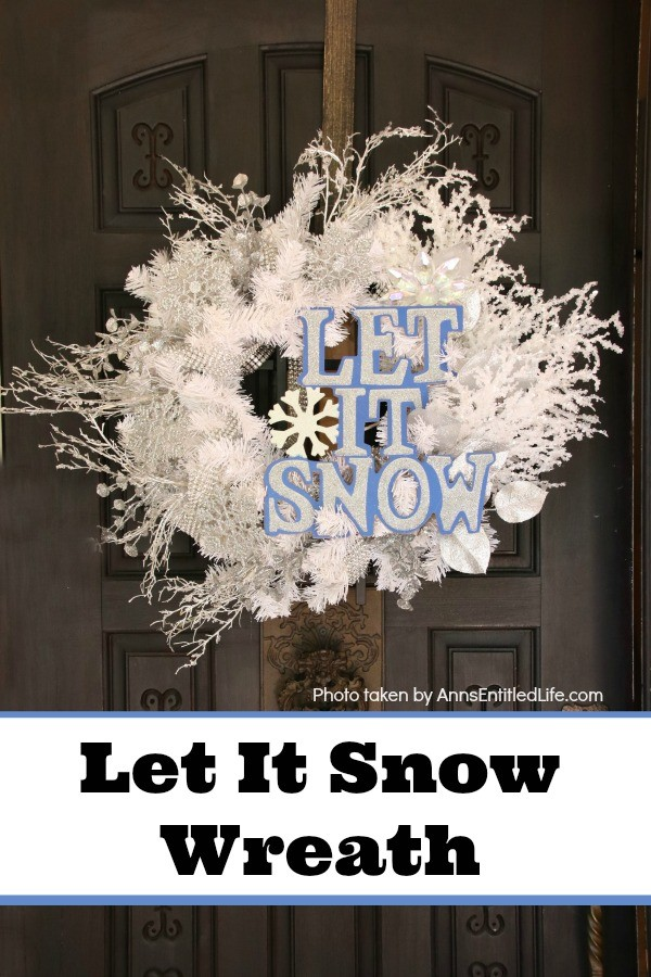 An excessively decorated white wreath (crystals, silver, rhinestones) with a let it snow sign, hanging from a bronze wreath hanger on a dark brown door.