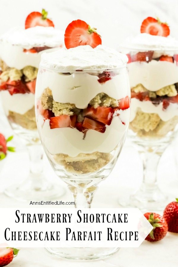 close-up of three strawberry cheesecake partfait desserts on a white background surrounded by fresh strawberries
