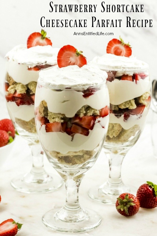 three strawberry cheesecake partfait desserts on a white background surrounded by fresh strawberries