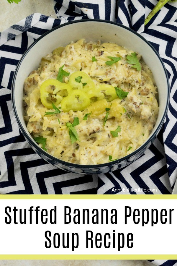 A black bowl with a white interior is filled with banana pepper soup, decorated with sliced banana peppers. This is set upon a black and white chevron napkin.