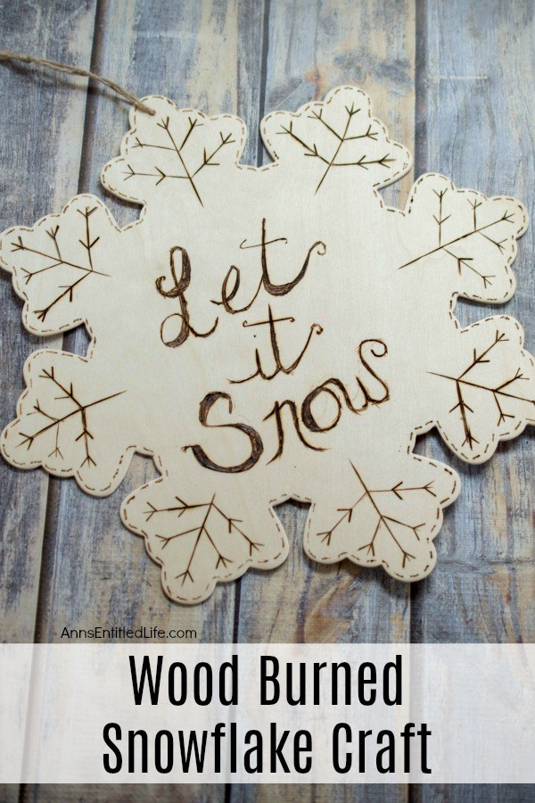 Wooden snowflake ornament etched with dashes, branches, and the words Let It Snow. There is a twine hanger at the end. This sits on top of a rustic blue surface.