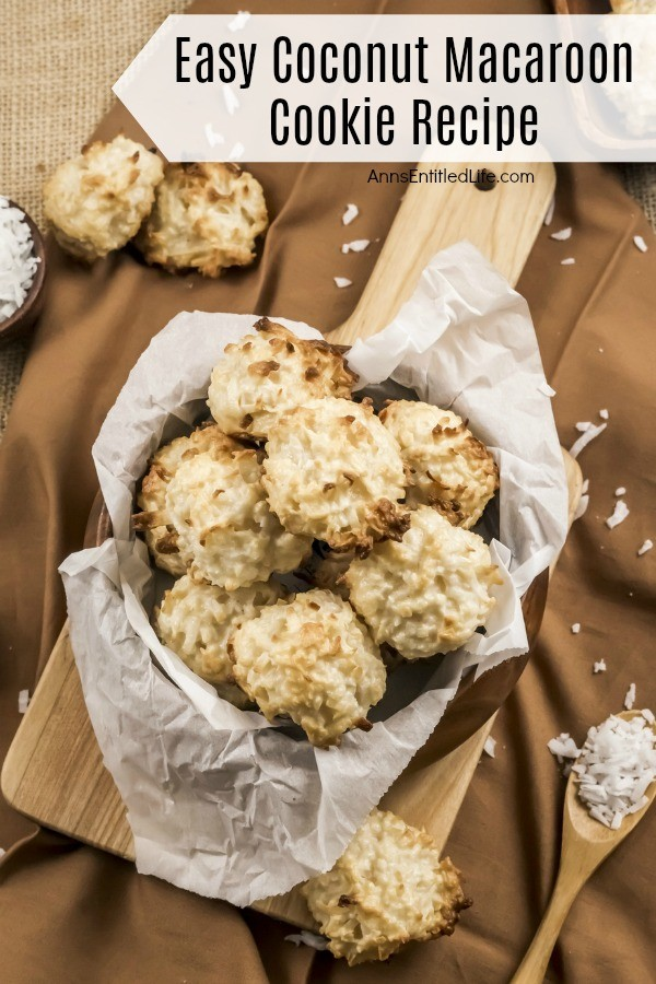 Overhead view of a wooden bowl of baked coconut macaroon cookies on a wooden server, coconut in a bowl in the upper left background, more coconut macaroons in a tray in the upper right background