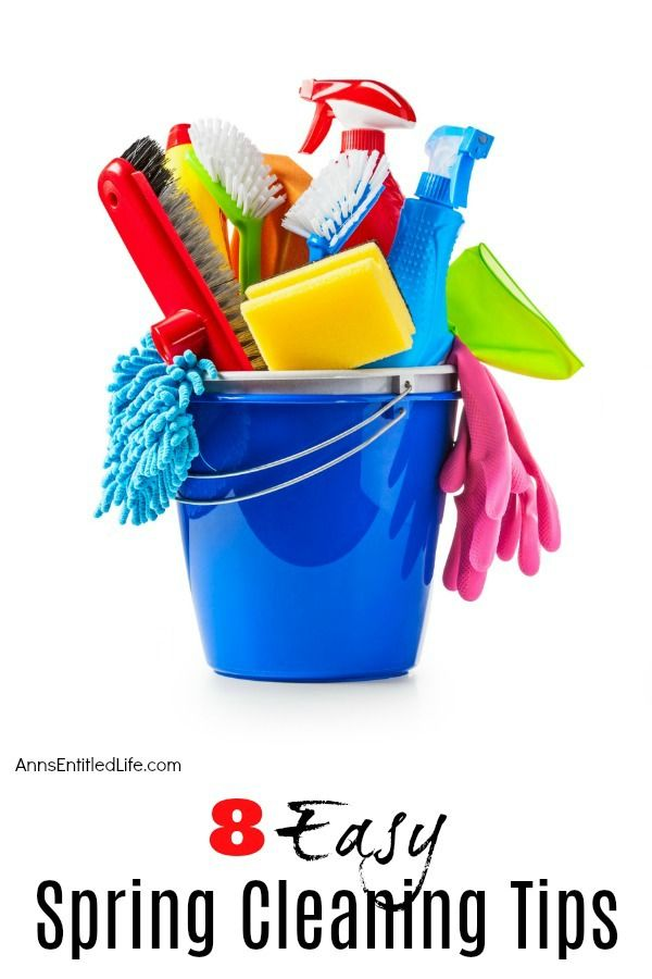 Blue bucket filled with household cleaning supplies including brushes, sponges, rags, and gloves.