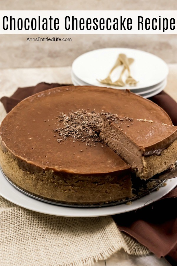 A whole chocolate cheesecake on a white serving plate. One piece is being lifted on a server, white cake plates with gold serving utensils are in the background.