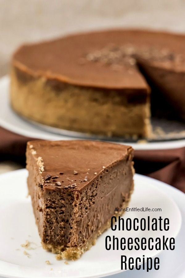 And piece of chocolate cheesecake with a bite removed on a white serving plate, the remainder of the chocolate cheesecake on a white serving plate in the background, all on top of a brown fabric.