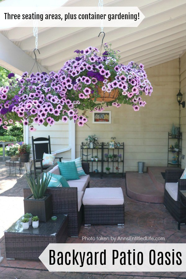 A backyard seating area with couch, and ottoman, chair, and rocking chair. There is an end table with a faux plant and three shelves with various floral. There are planters of flowers in the upper left, two purple petunia hanging baskets are in the foreground.