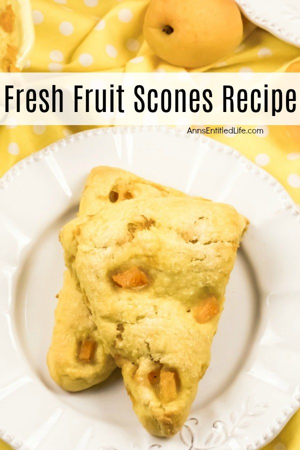 Two stacked apricot scones ona white plate, the white plate is on top of a yellow polka dot napkin. A fresh apricot is in the upper right.
