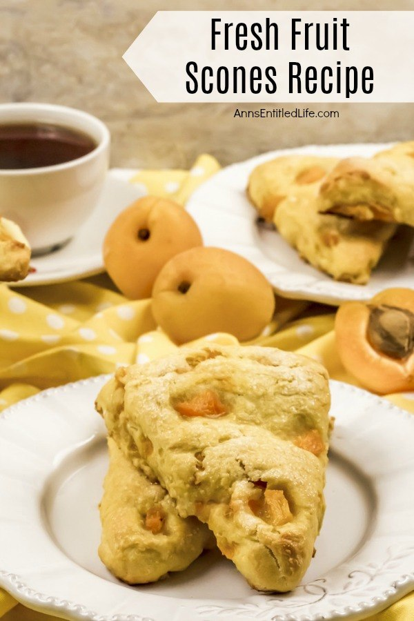Two stacked apricot scones ona white plate. Two whole apricots are shown in the upper left, a cup of black coffee it higher on the left side, one fresh apricot cut in half is in the upper right. More stacked apricot fruit scones are in the far upper right.