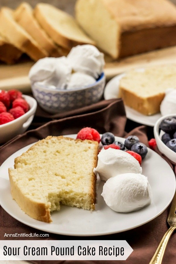 A white plate with a slice of sour cream pound cake with a bite removed, sour cream balls, blueberries and raspberries. A second such plate is in the upper right. Directly to the right is a bowl of blueberries. In the upper left are a bowl of raspberries and sour cream balls. At the top of the photo is the cut sour cream pound cake on a wooden cutting board.