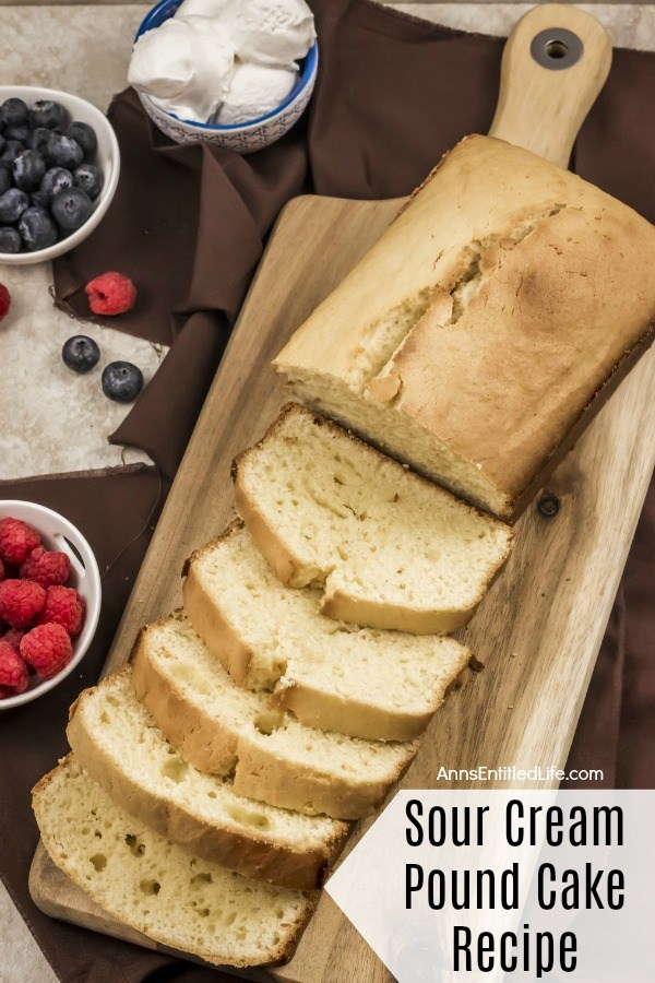 A sliced sour cream pound cake on a wooden cutting board. A bowl of raspberries to the left, a bowl of blueberry in the upper left, a bowl of source cream balls are above that, all on a dark-brown linen.
