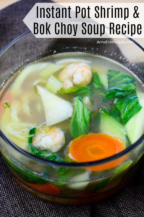 Close-up, overhead view of shrimp and boy choy soup in a clear bowl on a navy blue napkin